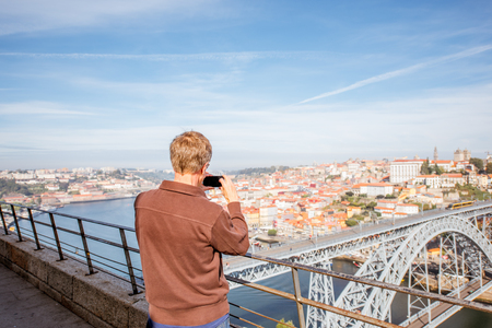 PORTO, PORTUGAL - September 24, 2017: Man photographing with phone aerial view on the Luis bridge on the Douro river in Porto city in Portugal