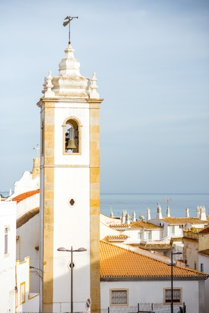 Cityscape view on the old town with beautiful white houses and bell tower in Albufeira city on the south of Portugal Фото со стока