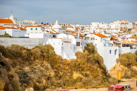 Cityscape view on the old town with beautiful white houses on the rocks in Albufeira city on the south of Portugal Фото со стока