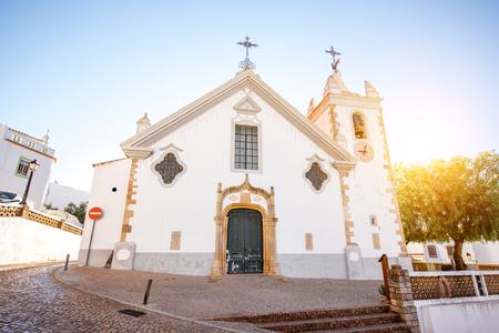 포르투갈의 남쪽에 일출 동안 흰 오래 된 교회와 전형적인 마을 스톡 콘텐츠