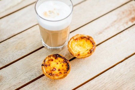 Portuguese coffee galao with sweet dessert pastel de Nata on the table outdoors