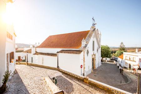 ポルトガル南部の日の出の間に白い古い教会を持つ典型的な村 写真素材