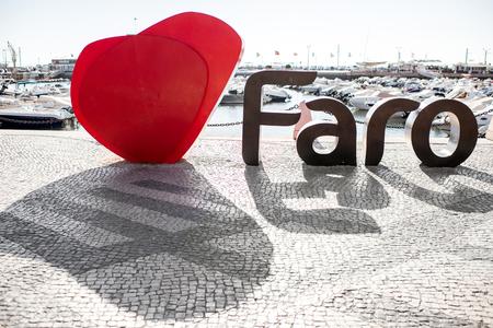 """FARO, PORTUGAL - 2 de octubre de 2017: Letras grandes del nombre de la ciudad de Faro con forma del corazón en la """"promenade"""" en Faro en el sur de Portugal Foto de archivo - 90560064"""