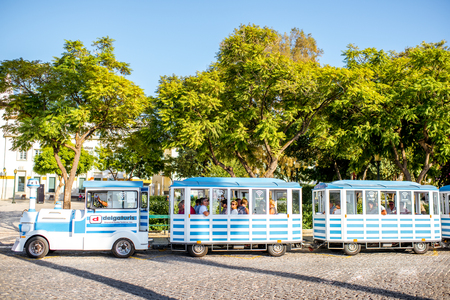FARO, PORTUGAL - October 02, 2017: Tourist bus standing near the park in the center of Faro city on the south of Portugal Редакционное