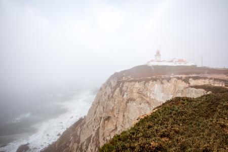 ポルトガルの霧の天候の間に灯台と岩の岬の眺め 写真素材 - 90613368
