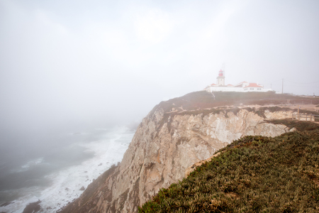 View on the Cape of the Rock with lighthouse during the foggy weather in Portugal Stock fotó