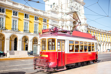 Old tourist tram on the central square with Augusta arch on the background in Lisbon, Portugal