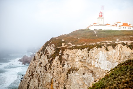 ポルトガルの霧の天候の間に灯台と岩の岬の眺め
