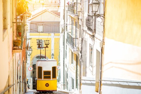 Street view with famous yellow funicular tram in Lisbon during the sunny day in Portugal Stock Photo