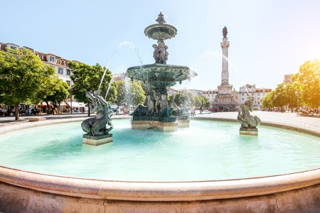Beautiful view on the fountain on the Rossio square with column during the sunny day in Lisbon city, Portugal