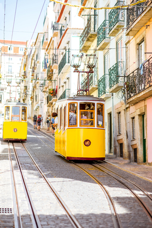 Street view with famous yellow funicular tram in Lisbon during the sunny day in Portugal Фото со стока