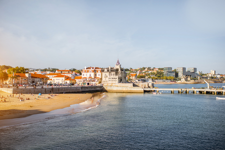 Sunset view on the beach with Palmela palace in Cascais resort in Portugal