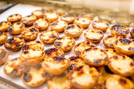Traditional portuguese creamy dessert Pastel de Nata on the showcase of the food store