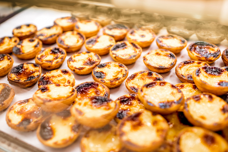 Traditional portuguese creamy dessert Pastel de Nata on the showcase of the food store