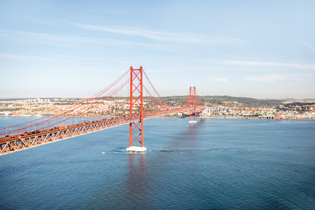 Landscape view on the Tagus river and the famous 25th of April Bridge during the morning light in Lisbon city, Portugal Banco de Imagens - 90667326