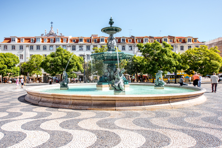 LISBON, PORTUGAL - September 27, 2017: Beautiful view on the fountain on the Rossio square with column during the sunny day in Lisbon city, Portugal