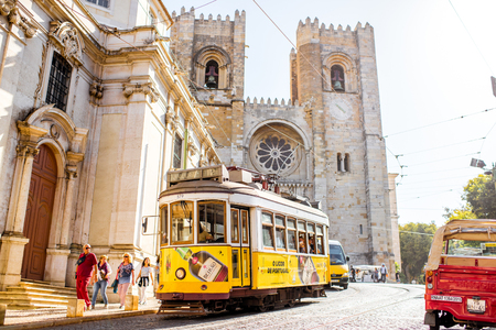 LISBON, PORTUGAL - September 28, 2017: Street view with famous old tourist tram full of people near the main cathedral in Lisbon city, Portugal Publikacyjne