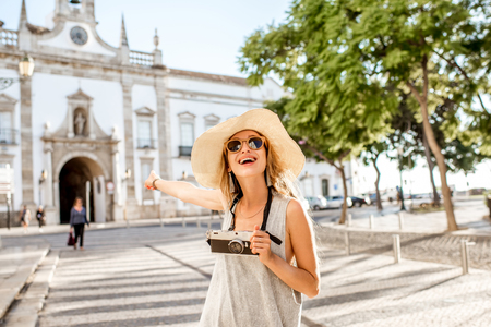 Portrait of a young woman tourist standing with photo camera on the city gate background in Faro town on the south of Portugal Foto de archivo - 90669595