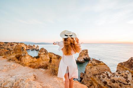 포르투갈의 남쪽에 라고스에서 일출 동안 바위 해안선에 좋은 전망을 즐기는 여자