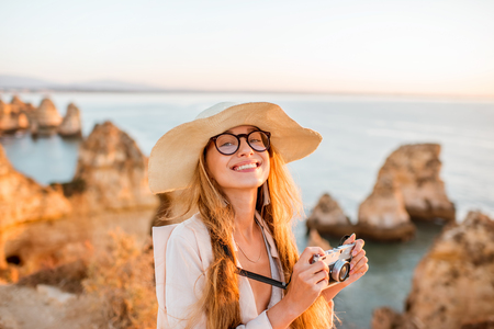 Portrait of a young woman with photo camera enjoying great view on the rocky coastline during the sunrise in Lagos on the south of Portugal Stock Photo