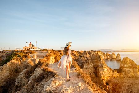 Vrouw die van groot uitzicht op de rotsachtige kustlijn geniet tijdens de zonsopgang in Lagos in het zuiden van Portugal