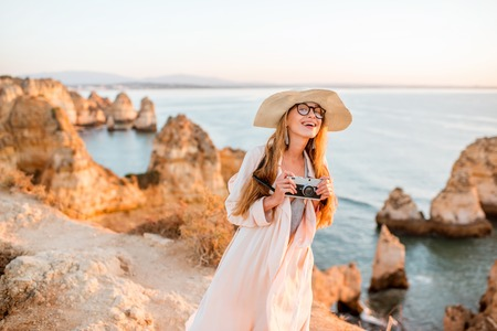 Portrait of a young woman with photo camera enjoying great view on the rocky coastline during the sunrise in Lagos on the south of Portugal 写真素材