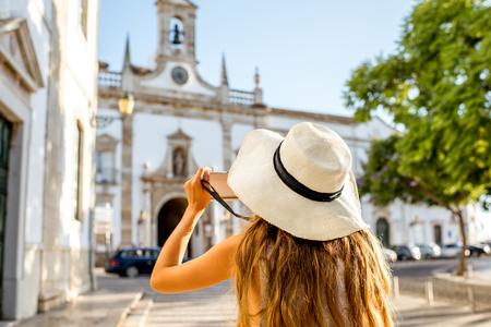 Turista de mujer joven de pie en el fondo de la puerta de la ciudad en la ciudad de Faro en el sur de Portugal Foto de archivo - 90669799