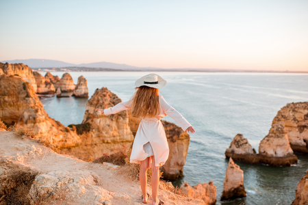 Woman enjoying great view on the rocky coastline during the sunrise in Lagos on the south of Portugal
