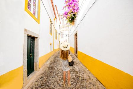 포르투갈에서 Evora의 오래 된 마을에서 거리를 여행하는 젊은 여자 스톡 콘텐츠