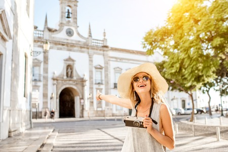 Portrait of a young woman tourist standing with photo camera on the city gate background in Faro town on the south of Portugal Foto de archivo - 92337202