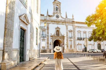 Young woman tourist standing on the city gate background in Faro town on the south of Portugal Foto de archivo - 90669818