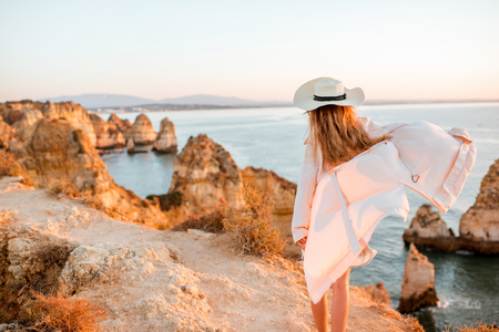 Woman enjoying great view on the rocky coastline during the sunrise in Lagos on the south of Portugal Stock Photo