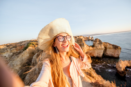 Young woman making selfie portrait on the rocky coastline during the sunrise traveling in Lagos on the south of Portugal