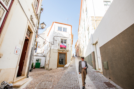 COIMBRA, PORTUGAL - September 26, 2017: View on the street with elder man walking in the old town of Coimbra city, Portugal