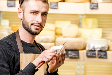 Portrait of a handsome seller in uniform cutting young cheese in front of the store showcase full of different cheeses Stok Fotoğraf