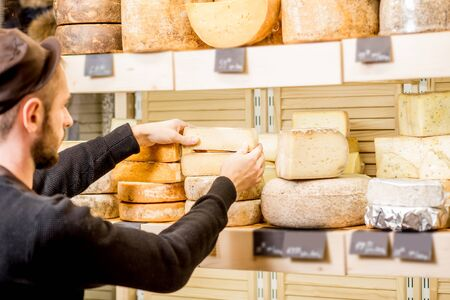Cheese seller putting goods on the shelves at the cheese store