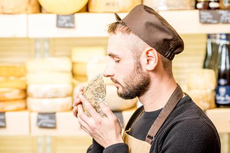 Portret van een knappe kaasverkoper in eenvormige ruikende gekruide kaas voor het hoogtepunt van de opslagshowcase van verschillende kazen Stockfoto - 90960541
