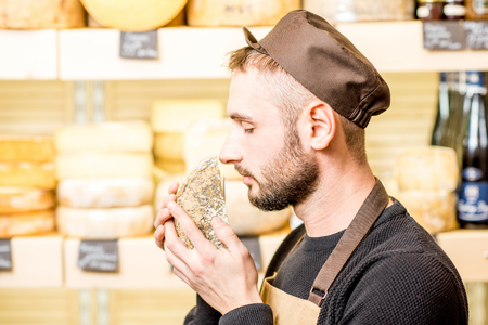 Portrait of a handsome cheese seller in uniform smelling seasoned cheese in front of the store showcase full of different cheeses Archivio Fotografico