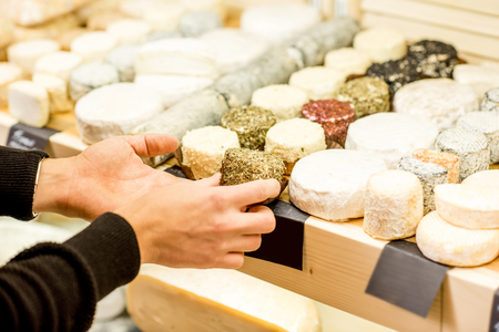 Kaasverkoper die goederen in de schappen legt bij de kaaswinkel