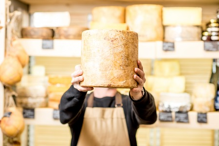 Portrait of a handsome cheese seller in uniform holding a big seasoned cheese in front of the store showcase full of different cheeses