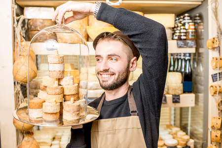 Portrait of a handsome cheese seller holding beautiful plate with a pile of cheeses in the shop