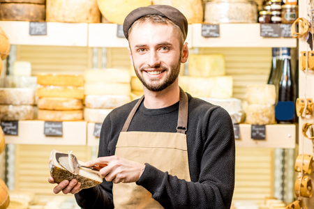 Portrait of a handsome cheese seller in uniform standing in front of the store showcase full of different cheeses