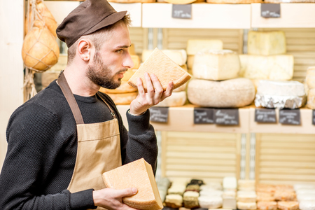 Portrait of a handsome cheese seller in uniform smelling seasoned cheese in front of the store showcase full of different cheeses Stock Photo