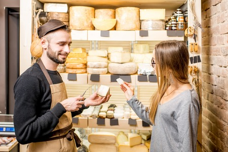 Salesman with a woman customer choosing a cheese for buying at the food store