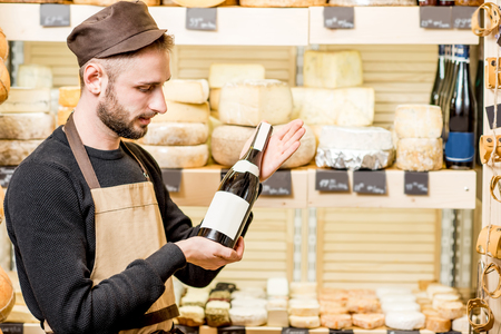 Portrait of a young sommelier in uniform standing with wine bottle in front of the store showcase full of different cheeses
