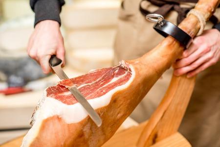 Corte com perna de prosciutto de faca longa na loja de comida Foto de archivo - 91309355