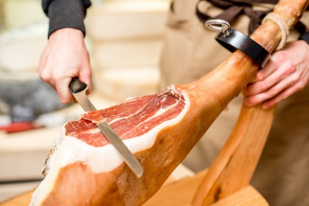 Cutting with long knife prosciutto leg in the food store