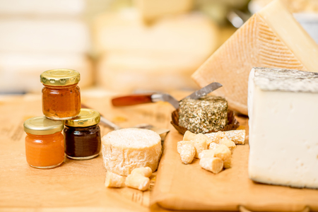Cheese assortment with sweet jams on the table in the cheese shop
