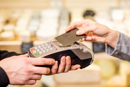 Vrouw die met kaart contactloos in de voedselopslag betaalt. Vergrote weergave van de terminal en kaart