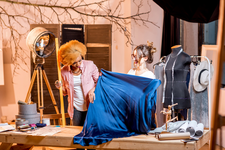 Two multi-ethnic female tailor working with blue fabric at the studio with different tailoring tools and clothes